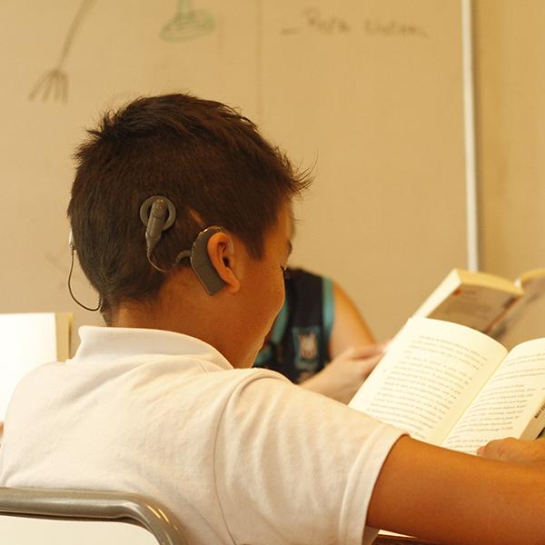 Niño hipoacúsico del Programa educativo primario leyendo en clase