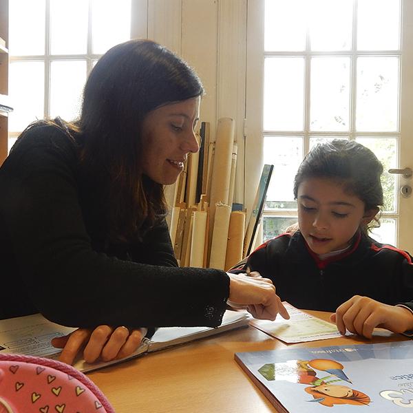 Niña hipoacúsica del Programa de integración haciendo la tarea junto a su docente.