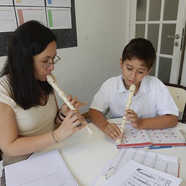 Niño hipoacúsico del Programa de integración practicando la flauta con su docente