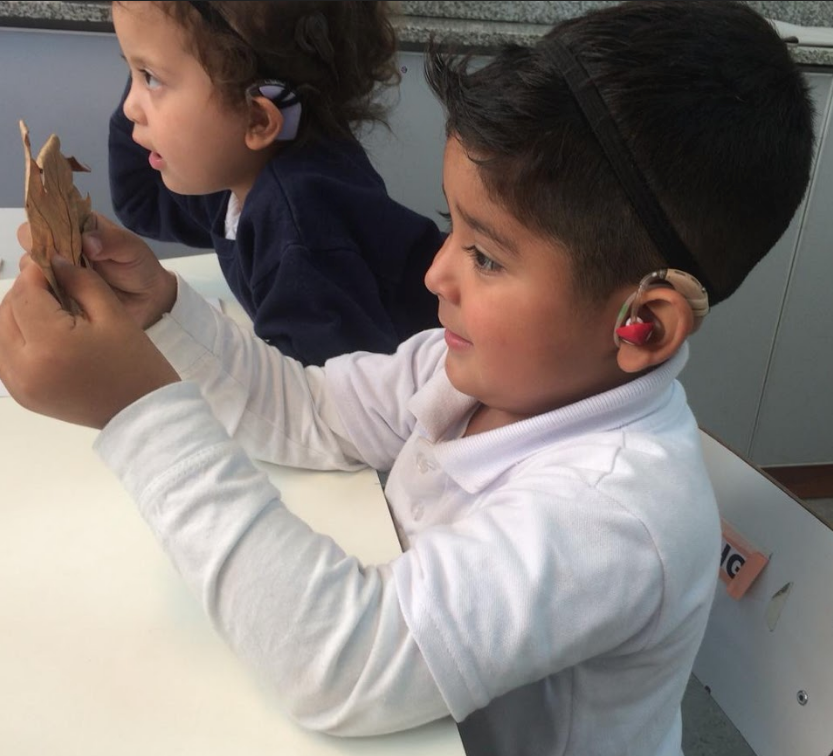 Niño hipoacúsico en clase trabajando con una hoja