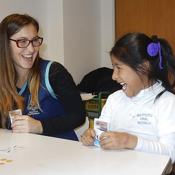 Niña hipoacúsica jugando a las cartas con su docente dentro del programa educativo inicial