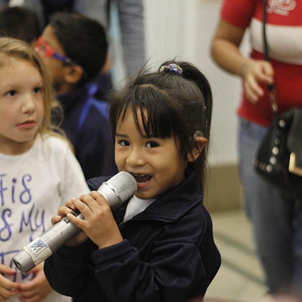 Niña hipoacúsica hablando con un micrófono en la bienvenida en el Programa educativo inicial.